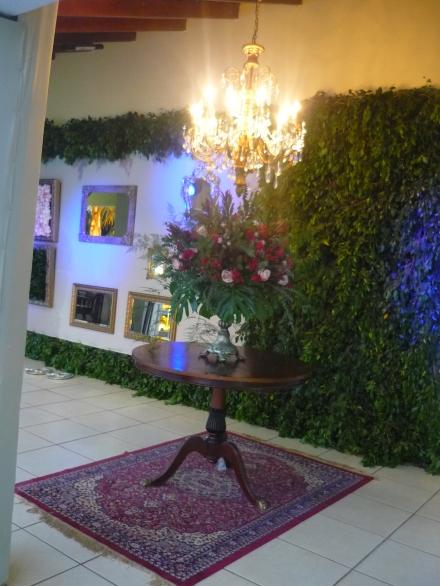 Entre as paredes foi montada essa mesa com um grande arranjo e um lindo lustre.